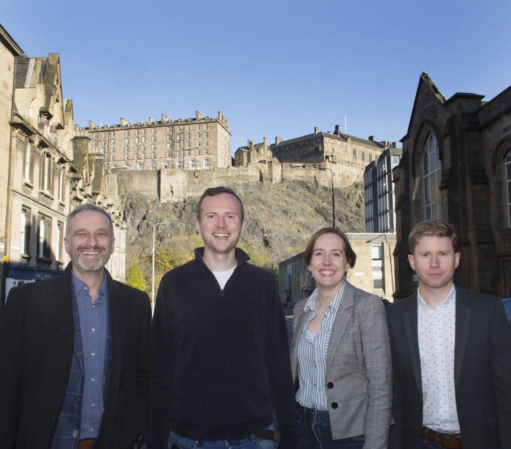 WhisperClaims team posing in front of Edinburgh Castle